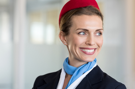 Cheerful flight attendant looking away. Portrait of happy flight assistant. Closeup face of mature woman airhostess wearing uniform and red cap with light blue scarf in airport. Banque d'images