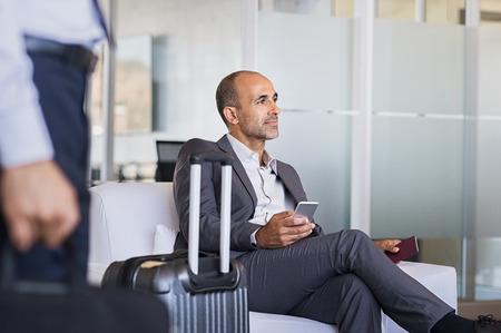 Rijpe zakenman die vliegtuig op de luchthaven verwacht. Nadenkende bedrijfsmens die op vlucht in luchthaven wacht. Formele bedrijfsmensenzitting in luchthavenwachtkamer met in hand bagage en telefoon. Stockfoto