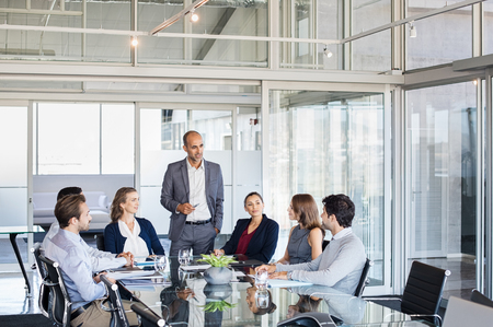 Human resource manager training people about company and future prospects. Group of businesspeople sitting in meeting room and listening to the speaker. Leader man training his work group in a conference room.
