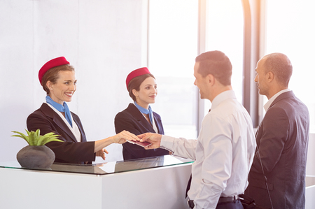 Luchtvaartmaatschappijen passeren in bij de luchtvaartmaatschappij. Jonge vrouw geeft paspoort en ticket terug naar zakenman bij luchthaven inchecken. Twee zakenlieden op luchthaven checkin bureau vertrekken op zakenreis. Stockfoto