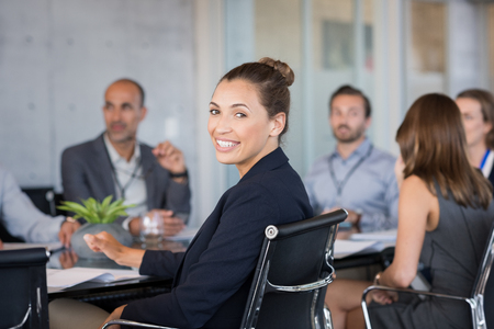 Young beautiful businesswoman with colleagues sitting in a modern board room. Proud smiling business woman sitting during a meeting and looking at camera. Portrait of a happy businesswoman with executives working. Banque d'images