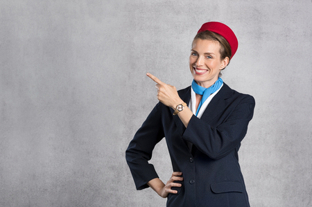 Portret van air hostess wijst tegen grijze achtergrond met kopie ruimte. Gelukkige vluchtassistent die aangeeft. Jonge vluchtluider op grijze achtergrond die iets toont terwijl u camera kijkt.