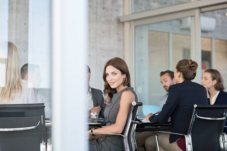 Young smiling business woman attending meeting in modern boardroom. Portrait of businesswoman looking at camera during conference. Satisfied beautiful businesswoman sitting at conference table with team. Banque d'images