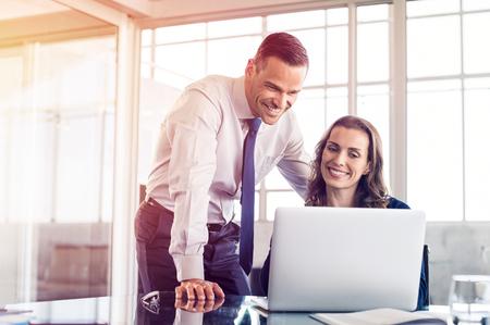 Jeune femme d'affaires montrant des informations sur un ordinateur portable à un homme d'affaires. Belle femme d'affaires expliquant un plan pour l'homme d'affaires sur ordinateur. Des collègues travaillent ensemble dans un bureau moderne. Banque d'images