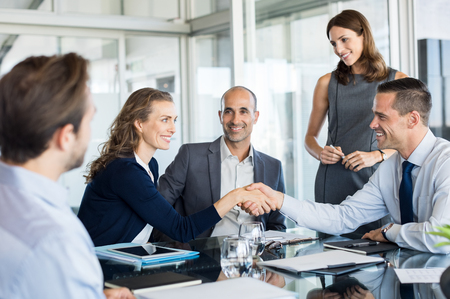 Handshake to seal a deal after a meeting. Two successful business people shaking hands in front of their colleagues. Mature businesswoman shaking hands to seal a deal with smiling businessman. Banque d'images