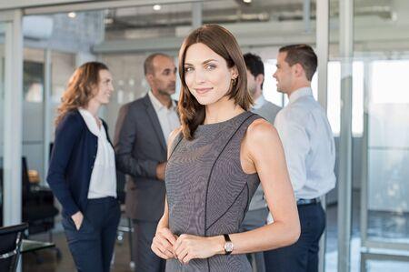 Une femme formelle réussi debout devant les gens d'affaires et souriante. Portrait d'une femme d'affaires confiant et fier avec une équipe d'affaires au bureau moderne. Belle femme d'affaires satisfaite à la caméra.