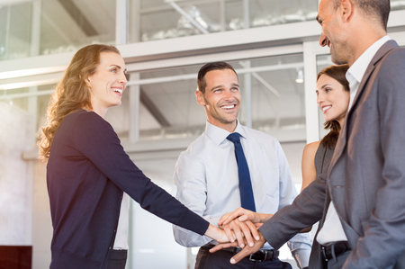 Successful business people stacking hands in modern office. Successful business team celebrating victory at work. Businessmen and businesswomen join hand while meeting in modern boardroom.
