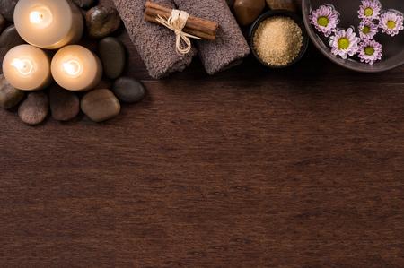 갈색 수건와 나무 배경에 꽃과 물 그릇 스파 설정의 상위 뷰. 나무 테이블에 촛불에 자연 스파 설정의 높은 각도보기. 텍스트를위한 공간을 복사합니다