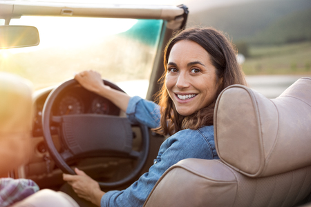 Happy woman holding steering wheel ready to drive and looking back. Smiling mature woman driving convertible car and looking at camera. Carefree woman enjoying driving in a cabriolet. Stock Photo