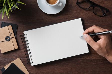 Vue de dessus d'homme d'affaires écrit sur un cahier vierge. Vue d'angle élevé de main d'homme écrivant sur le bloc-notes vide avec des lunettes, tasse à café et dossier sur la table en bois. Gros plan de main d'homme d'affaires, prendre des notes.