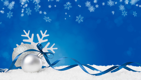 Christmas background in blue. Snow flakes and christmas balls with ribbon and copyspace. Xmas background with snowflakes, balls and ribbon. Write it on whatever you need. Standard-Bild