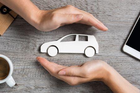 Mains protégeant l'icône de la voiture sur une table en bois. Vue de dessus des mains montrant le geste de protection de la voiture. Assurance automobile et concept d'entreprise automobile.