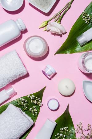 Vue de dessus des produits cosmétiques sur fond rose avec des feuilles et des fleurs blanches. Vue d'angle élevé des produits de soins de la peau ou du spa. Poudre d'argile, lotions, serviette, avec des feuilles et des fleurs sur fond rose.