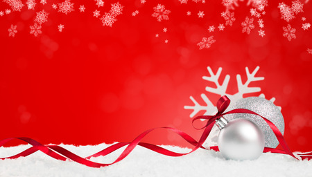 Christmas background in red. Snow flakes and christmas balls with ribbon and copyspace. Xmas background with snowflakes, balls and ribbon. Write it on whatever you need.