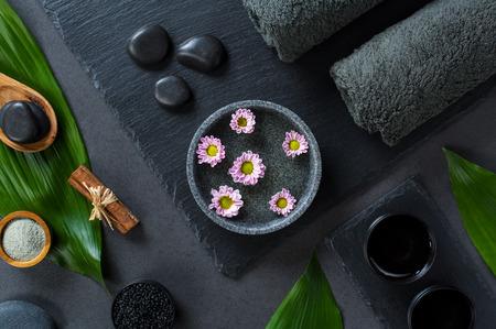 Vue grand angle du cadre de spa beauté avec des fleurs roses flottant dans l'eau. Vue de dessus de manucure avec de petites marguerites dans l'eau et des pierres chaudes. Deux serviettes roulées avec une feuille verte sur le tableau noir.