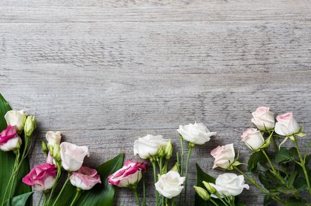 Roses blanches et roses sur un fond en bois clair avec espace copie. Vue de dessus de belles fleurs fraîches avec des feuilles vertes sur la table de fleuriste. Vue d'angle élevé de composition de fleurs romantiques pour la Saint-Valentin ou le jour du mariage.