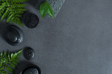 Top view of spa setting with wet hot stones and green ferns on gray background with copy sapce. High angle view of stacked black stones for massage with drops of water and grey rolled towel on blackboard. Luxury and elegant wellness concept.