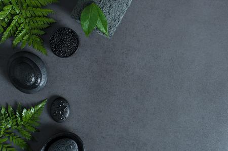 Vue de dessus du cadre de spa avec des pierres chaudes et humides et des fougères vertes sur fond gris avec copie sapce. Vue d'angle élevé de pierres noires empilées pour massage avec des gouttes d'eau et une serviette roulée grise sur tableau noir. Concept de bien-être luxueux et élégant. Banque d'images