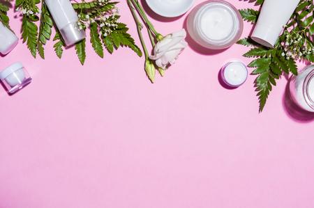 Vue de dessus du fond rose avec des produits cosmétiques, des fleurs et des feuilles de fougère. Vue d'angle élevé des produits de soins de la peau et crème hydratante isolé sur fond rose avec espace copie. Lotion pour le corps et produits de mode.