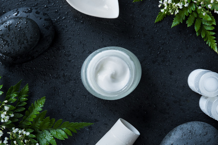 Moisturizer jar with white tubes of lotion and basalt rock on black background. Spa massage cream on wet slate ready for therapy. Natural fresh facial moisturizer facial in a glass, cosmetic and spa concept.