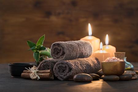 Serviettes brunes avec bambou et bougies pour un massage relaxant et un soin du corps. Belle composition avec des bougies, des pierres de spa et du sel sur fond en bois. Cadre de spa et de bien-être prêt pour un traitement de beauté.