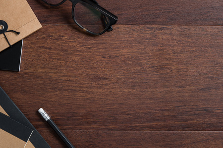 Top view of glasses and recycled notepad on wooden desk with copy space. High angle view of spectacles on wooden table with office supplies. Flat vision of wooden desk of student.