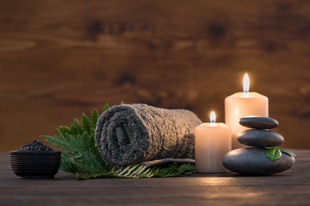 Brown towel on green fern with candles and black hot stone on wooden background. Hot stone massage setting lit by candles. Hot stone therapy for one person with candle light. Beauty spa treatment and relax concept. Stock Photo - 87636887