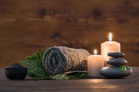 양 초와 나무 배경에 검은 뜨거운 돌 녹색 펀에 갈색 수건. 뜨거운 돌 마사지 설정 촛불에 의해 점화. 촛불을 가진 한 사람의 뜨거운 돌 치료. 아름다움 스파 트리트먼트 및 개념을 긴장.
