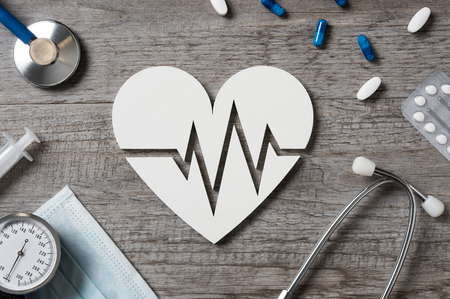 Top view of doctor desk with heart shape showing cardiac signs, medicine and stethoscope. High angle view of white shaped heart icon with electrocardiogram. Cardiology and healthcare concept. Banque d'images