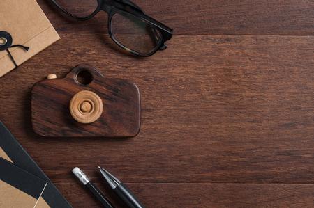 Vue grand angle du bureau de photographe avec équipement de bureau et des lunettes. Vue de dessus de table en bois de style vintage avec des lunettes, bloc-notes recyclé et caméra en bois originale. Bureau de voyageurs avec espace copie.