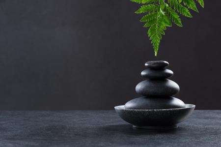 Concept de spa élégant et luxueux avec des pierres de spa et des feuilles de fougère. Pierres chaudes sur plan d'ardoise avec fond noir et espace copie. Une goutte d'eau glisse d'une feuille de fougère humide sur une pile de pierres noires pour le massage.