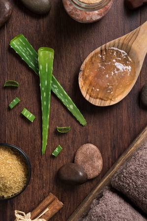 Stem of aloe vera plant on wooden background with himalayan salt and stones. Top view of aloevera gel on wooden spoon with beauty spa setting on table. High angle view of beauty treatment at sap salon.