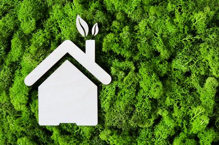 Draufsicht der hölzernen Form des Hauses auf grünem Moos mit Kopienraum. Hohe Winkelsicht des Öko-Hauses und der Blätter. Umweltschutz und nachhaltige Architektur und Energiekonzept. Standard-Bild