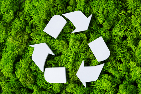 Top view of white recycle eco symbol on green moss with copy space. High angle view of recycled sign and eco concept on green background. Recycling and conservation of the environment sign.