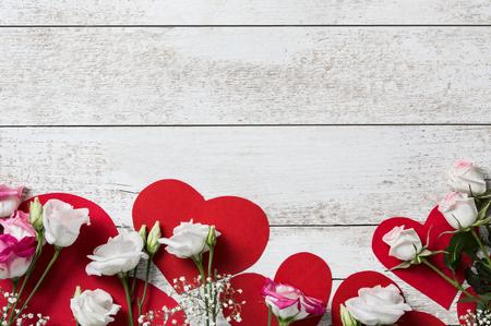 Vue de dessus de belles fleurs sur des coeurs rouges sur une table en bois vintage. Saint-Valentin avec des roses blanches sur les coeurs rouges. Vue d'angle élevé de roses blanches et roses sur un fond en bois clair.