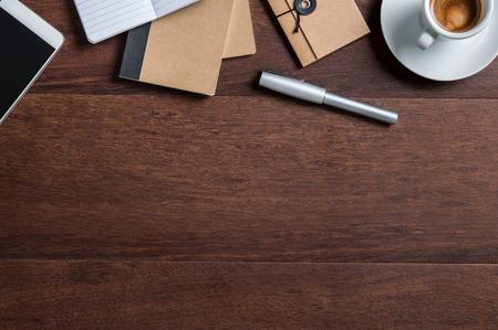 Vue de dessus du bureau d'affaires avec tasse de café, smartphone, agenda et stylo. Vue d'angle élevé de la table en bois de bureau avec espace copie. Vue à plat du bureau professionnel avec des fournitures de bureau.
