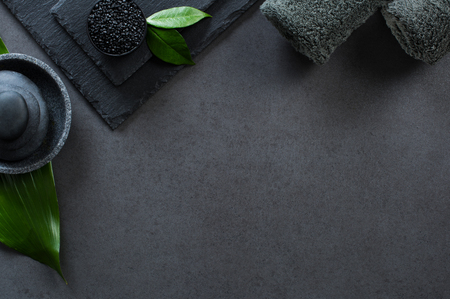 Top view of two gray rolled towels with hot stones pile with copy space. High angle view of male beauty treatment set with green leaf and black salt. Luxury and elegant spa setting on black background.