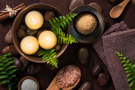 Beautiful spa composition on wooden background with floating candles in a water bowl. Burning candles with himalayan salt and spa products on brown background. Luxury spa set with towels and fern leaves.