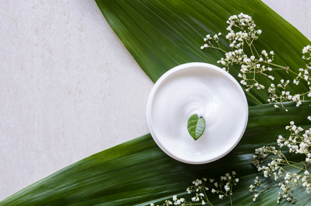 Top view of cosmetic lotion with white flowers and green leaf. Skin care beauty treatment with jar of body moisturizer. High angle view of white body lotion with little green leaf on marble background. Stockfoto