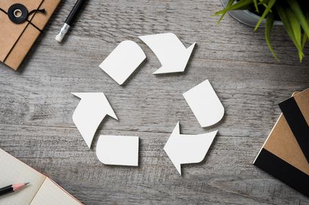 Vue de dessus de recycler signer sur une table en bois vintage avec équipement de bureau. Vue grand angle du logo de recyclage avec du papier recyclé et bloc-notes sur le bureau d'affaires. Symbole de recyclage et concept environnemental.
