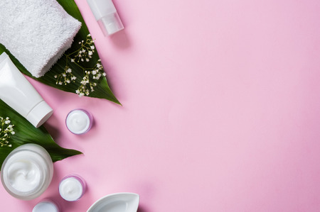 Top view of spa treatment products on light pink background. High angle view of moisturizing cream in a jar with beauty products on green leaves. Corner of woman accessories with copy space.