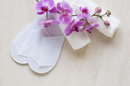 Top view of hotel slippers with white towels and orchid. Hotel set of two towels on elegant marble. High angle view of beautiful orchids on towels and scuff on marble background.