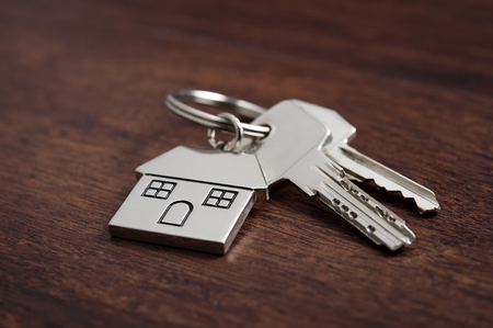 Close up of house keys on a house shaped keychain on wooden background. Concept for real estate, moving home or renting property on dark wood.