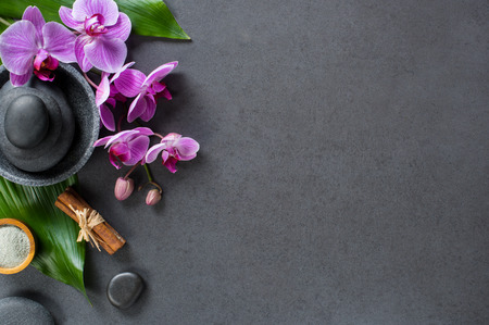 Top view of hot stones setting for massage treatment on blackboard with copy space. High angle view of beautiful orchids on green leaf with black stones pile for spa therapy. Elegant and luxury spa concept on gray background.