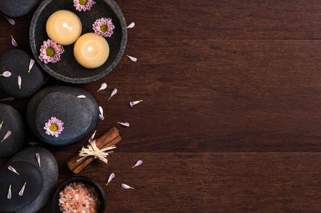 Vue de dessus de deux bougies brûlants avec des pétales de fleurs roses et de sel sur fond en bois. Thérapie de Lastone et des bougies flottantes avec des marguerites sur la table en bois. Vue grand angle du spa avec espace copie.