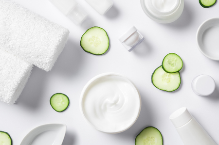 vysoký úhel pohledu: Top view of cosmetic products with slices of cucumber and towels on white background. High angle view of beauty products. Moisturizer and other skincare products with napkin on white background.