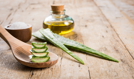 Close up of aloe vera leaves and essential oil on wooden background. Spa and beauty treatment concept with green aloe vera on wooden spoon. Fresh slices of aloe with essential oil.