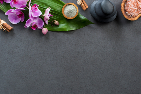Top view of spa setting with hot stones, orchids and pink salt. High angle view of orchids with green leaf on blackboard with stacked hot stone for massage treatment. Luxury and elegant spa set with copy space. Stock Photo - 87636905
