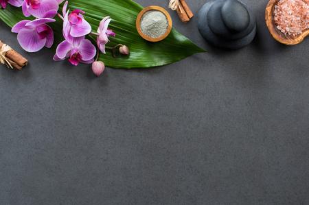 Vue de dessus du cadre de spa avec des pierres chaudes, des orchidées et du sel rose. Vue d'angle élevé d'orchidées avec feuille verte sur tableau noir avec pierre chaude empilée pour le traitement de massage. Luxe et élégant spa avec espace copie. Banque d'images