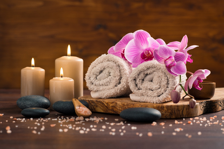 Spa setting with brown rolled towel, orchids and candles on wood. Relaxing spa concept with candles, towels and hot stones massage with himalayan pink salt. Beautiful composition for beauty treatment in a spa. Stock Photo - 87636907